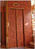 Custom landing door, fully panelled in burl plastic laminate with glossy gilded stainless-steel finish